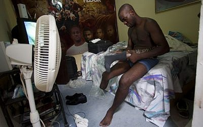 Dancer Georges Exantus prepares to put on his prosthetic limb in his bedroom as he prepares for his wedding in Port-au-Prince, Haiti on Sunday, Jan. 20 (photo credit: AP/Dieu Nalio Chery)