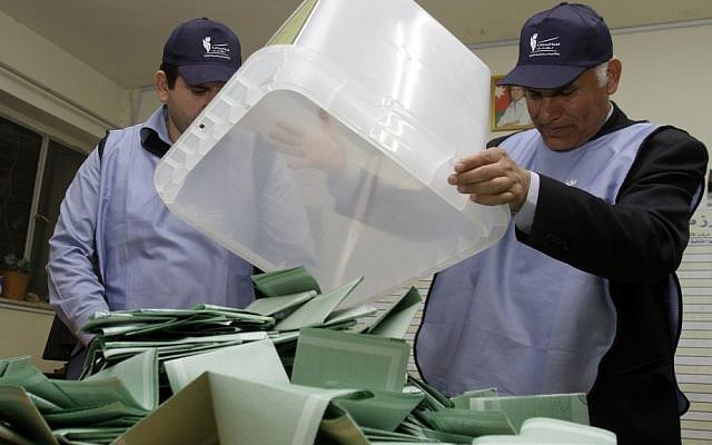 Jordanian officials empty a ballot box in Amman, Wednesday (photo credit: Raad Adayleh/AP)
