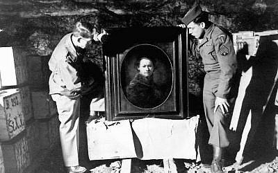 Two US soldiers, shown in 1945 or 1946 inspecting a Rembrandt self-portrait in a salt mine where the Nazis stored stolen and hidden art (Courtesy National Archives and Records Administration)