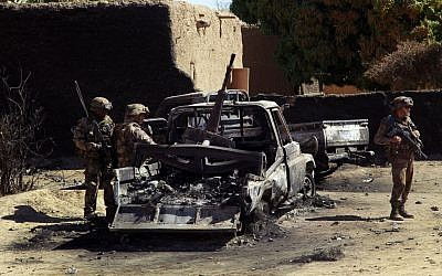 French troops inspect the charred remains of military vehicles used by radical Islamists on the outskirt of Diabaly, Mali on Monday Jan. 21, 2013 (photo credit: AP/Jerome Delay)