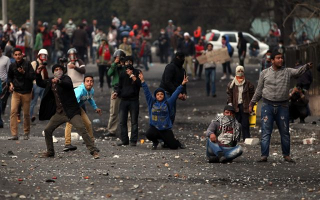 Egyptian protesters clash with riot police, not seen, near Tahrir Square, Cairo, Egypt, Tuesday, Jan. 29, 2013 (photo credit: AP/Khalil Hamra)