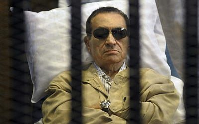 Egypt's ex-president Hosni Mubarak lies on a gurney inside a barred cage in the police academy courthouse in Cairo, Egypt, June 2012. (photo credit: AP)