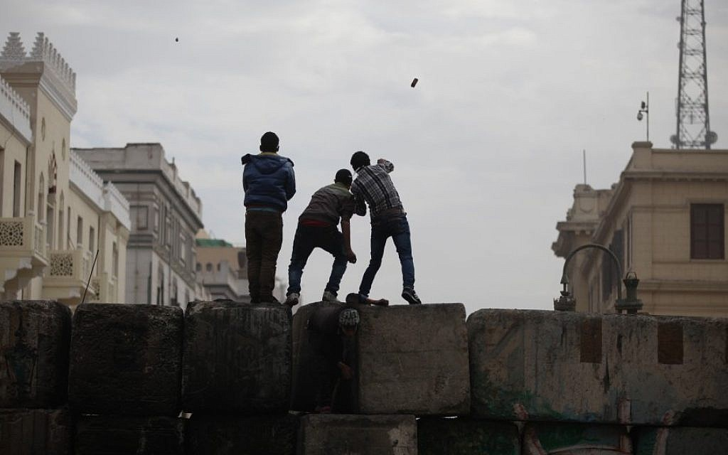 Skirmishes break out between protesters and security forces, unseen, near Tahrir Square, Cairo, Egypt, Friday. (AP Photo/Khalil Hamra)