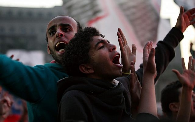 Egyptian protesters chant slogans as thousands of soccer fans of Egypt's most popular team, Al-Ahly, rally in Tahrir Square, the focal point of the Egyptian uprising, in Cairo, Egypt, Friday, Jan. 18, 2013. Fans called for revenge a week before the court was expected to give its verdict over last year's Port Said football stadium disaster, which killed 74 fans. (Photo credit: AP/Khalil Hamra)