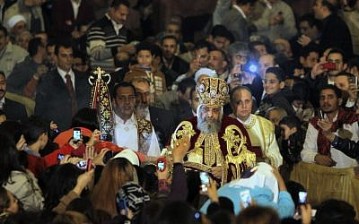 Pope Tawadros II, the 118th pope of the Coptic Church of Egypt, is greeted by Egyptian Christians as he prepares to lead a midnight Mass at St. Mark's Cathedral in Cairo, Egypt, in January (photo credit: AP/Amr Nabil)