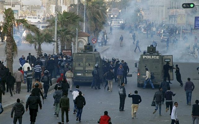 Police and protesters clashing outside a courtroom in Alexandria, Egypt in 2013 (photo credit: AP/Ahmed Ramadan)