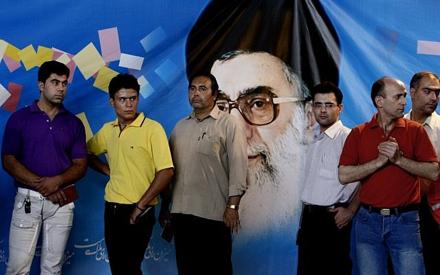 Iranian men line up as they wait to vote for presidential election, while they stand in front of a picture of the supreme leader Ayatollah Ali Khamenei, at a polling station, in downtown in Tehran in 2009. (photo credit: AP/Vahid Salemi)