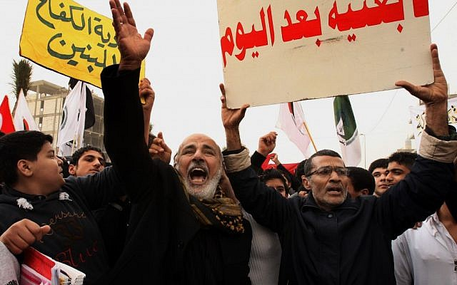Protesters chant pro-Iraqi Prime Minister Nouri al-Maliki slogans during a demonstration in Basra, Iraq, on Tuesday, January 8, 2013. The poster on the right reads, 'No Baathists after today.' (photo credit: AP/Nabil al-Jurani)