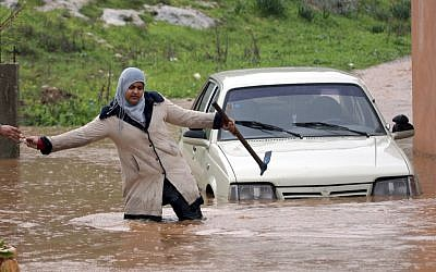 A Palestinian woman passes keys to a person on the other side of a flooded road in the West Bank city of Jenin, on Tuesday, Jan. 8 (photo credit: AP/Mohammed Ballas)