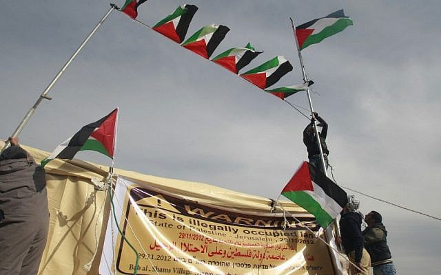 Pro-Palestinian activists place Palestinian flags in the new outpost of Bab el-Shams (Gate of the Sun) in the area known as E1, near Jerusalem, Saturday. (photo credit: AP)
