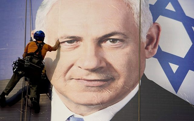 A man hangs a huge poster with an image of Prime Minister Benjamin Netanyahu overlooking the Ayalon freeway in Tel Aviv on Thursday (photo credit: AP/Ariel Schalit)