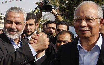 Gaza's former Hamas prime minister Ismail Haniyeh, left, greets Malaysian Prime Minister Najib Razak, right, after his arrival in Gaza City on Tuesday, January 22, 2013. (photo credit: AP Photo/ Mohammed Salem, Pool)