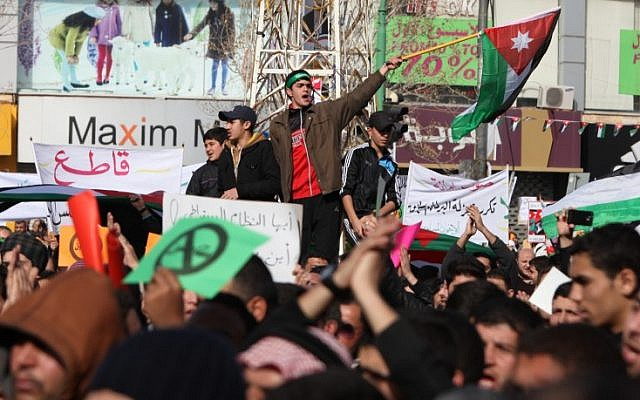 Demonstrators wave the Jordanian flag during a protest by the Muslim Brotherhood movement and other opposition parties against parliamentary elections in Amman, Jordan, in January 2013. (photo credit: AP)