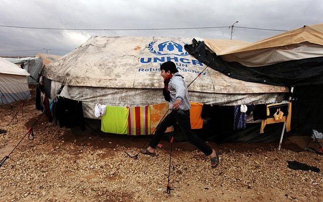 A Syrian refugee boy runs to his family tent at Zaatari Syrian refugee camp, near the Syrian border in Mafraq, Jordan, on January 8, 2013. (AP Photo/Mohammad Hannon)