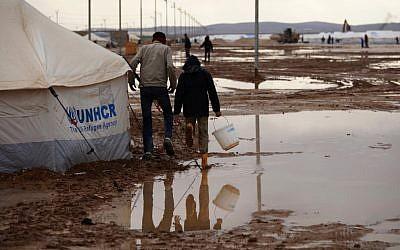 Syrian refugees walk through water and mud in the Zaatari Syrian refugee camp, near the Syrian border in Mafraq, Jordan, Tuesday, Jan. 8, 2013. (photo credit:AP /Mohammad Hannon)