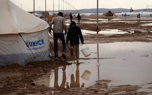 Syrian refugees walk through water and mud in the Zaatari Syrian refugee camp, near the Syrian border in Mafraq, Jordan, Tuesday, Jan. 8, 2013. (photo credit:AP /Mohammad Hannon)