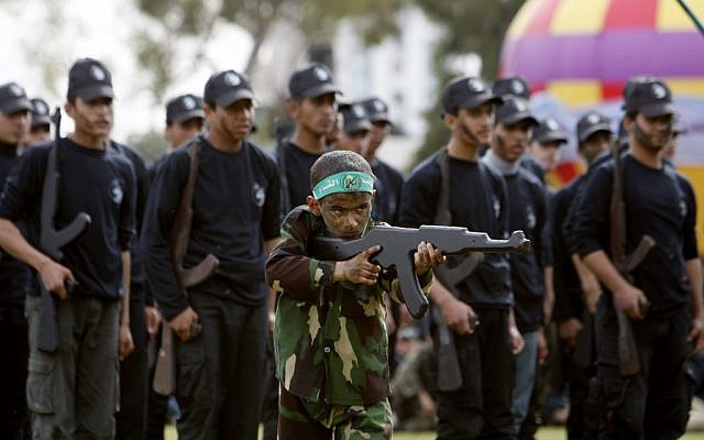 A Palestinian boy pretends to fire a rifle-shaped wooden stick during a graduation ceremony for the first group of school children's military training organized by Hamas  in Gaza City, Thursday, Jan. 24 (photo credit: AP/Adel Hana)
