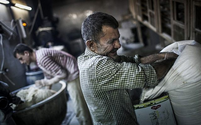 Men make bread at a bakery in the old city of Aleppo (photo credit: Andoni Lubaki/AP)