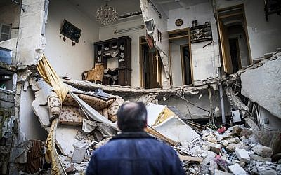 A civilian looks at a destroyed home in Aleppo, Syria, Thursday, Jan. 3, 2013 (photo credit: AP/Andoni Lubaki)