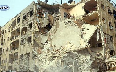 This photo released by the Syrian official news agency, SANA, shows damage caused to a building after a rocket slammed into it, killing at least 12 people, in Aleppo, Syria, Friday. (AP Photo/SANA)