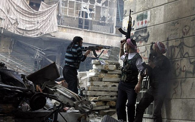 Free Syrian Army fighters fire at enemy positions during heavy clashes with government forces, in the Salaheddine district of Aleppo, Syria, Saturday, Dec. 29, 2012 (photo credit: AP/Abdullah Al-Yasin)
