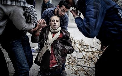 Men help a wounded civilian after a mortar attack in the Saif al-Dawlah neighborhood of Aleppo, Syria, Sunday, Jan. 13, 2013 (photo credit: Andoni Lubki/AP)