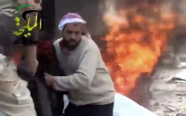 This image shows a wounded man being pulled from the site of a Syrian government airstrike on a gas station in the eastern Damascus suburb of Mleiha, Syria, on Wednesday, January 2, 2013. (photo credit: AP Photo/Shaam News Network via AP video)