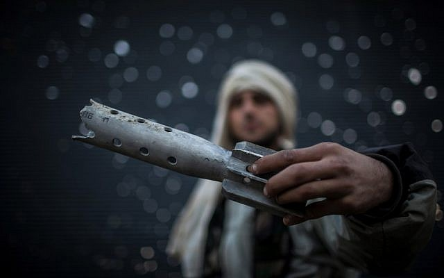 A Free Syrian Army fighter displays damaged ordnance in Aleppo, Syria, Tuesday, Jan. 15, 2013 (photo credit: Andoni Lubaki/AP)