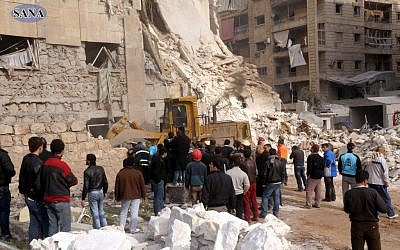This photo released by the Syrian official news agency, SANA, shows rescue workers and bystanders at a building damaged by a rocket attack that killed at least 12 people in Aleppo, Syria, Friday. (AP Photo/SANA)
