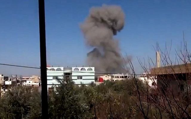 In this image taken from video obtained from the Ugarit News, which has been authenticated based on its contents and other AP reporting, smoke rises after an airstrike hit Daraa, Syria, on Monday, Jan. 14, 2012 (photo credit: Ugarit News via AP video/AP Photo)