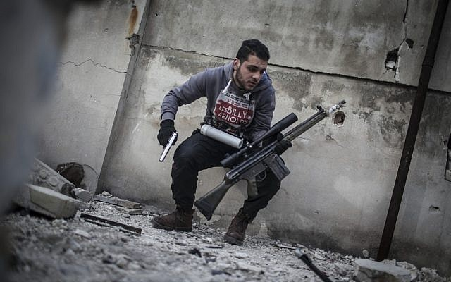 In this Friday, Jan. 18, 2013 photo, a sniper takes position on a roof during combat in the neighborhood of Saif Al-Dawlah in Aleppo, Syria (photo credit: AP/Andoni Lubaki)