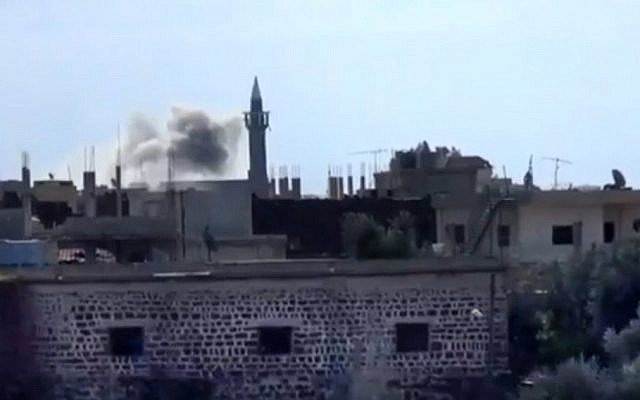 In this image captured from a video obtained from the Shaam News Network, which has been authenticated based on its contents and other AP reporting, smoke rises from buildings due to heavy shelling in Daraa, Syria, Thursday (AP Photo/Shaam News Network via AP video)