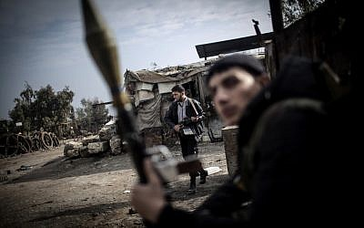 Free Syrian Army fighters hold their weapons during heavy clashes with government forces in Aleppo, Syria, on Sunday, January 20, 2013. (photo credit: AP/Andoni Lubaki)