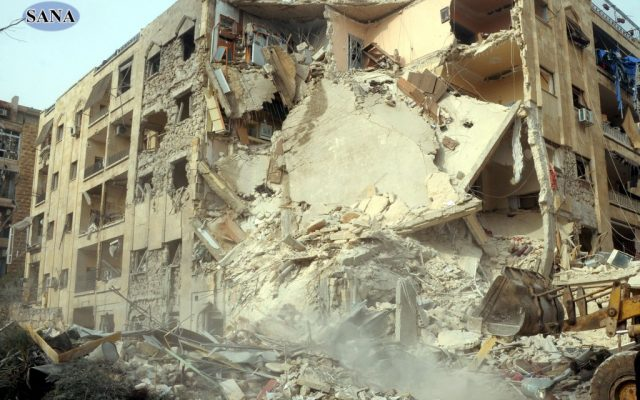 This photo released by the Syrian official news agency SANA, shows damage after a rocket slammed into a building, killing at least 12 people, in Aleppo, Syria, Friday, Jan. 18, 2013 (photo credit: AP/SANA)