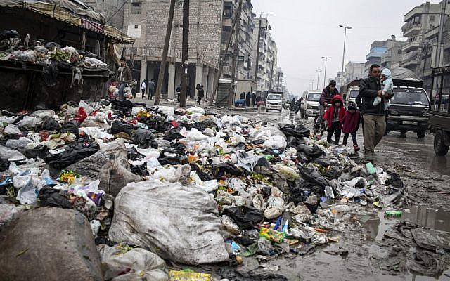 A family crosses a street piled with rubbish in Aleppo, Syria, Saturday, Jan. 5, 2013 (photo credit: AP/Andony Lubaki)