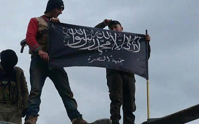 Syrian rebels from al-Qaeda affiliated Jabhat al-Nusra, wave their brigade flag as they step on the top of a Syrian air force helicopter, at Taftanaz air base that was captured by the rebels, in Idlib province, northern Syria, Friday January 11 2013 (photo credit: AP/Edlib News Network ENN)