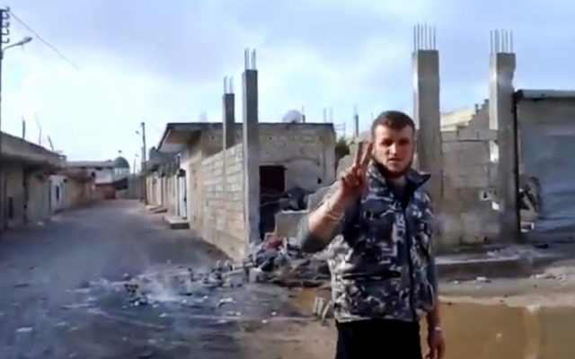 A Free Syrian Army soldier flashes the victory sign in Hama, Syria, January 2013 (photo credit: AP Photo/Ugarit News via AP video)