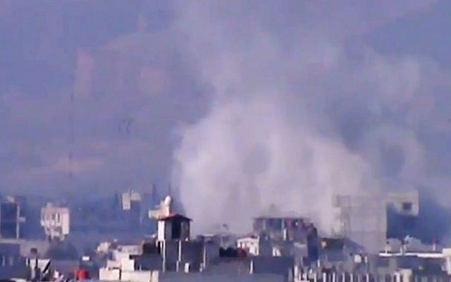 Smoke rises from buildings due to heavy shelling in Damascus countryside, Syria, on Wednesday, January 2, 2013. (photo credit: AP Photo/Shaam News Network via AP video)