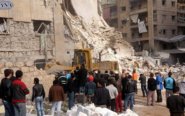 Rescue workers and bystanders surround a building damaged by a rocket attack, that killed at least 12 people, in Aleppo, Syria, on Friday (photo credit: AP/SANA)