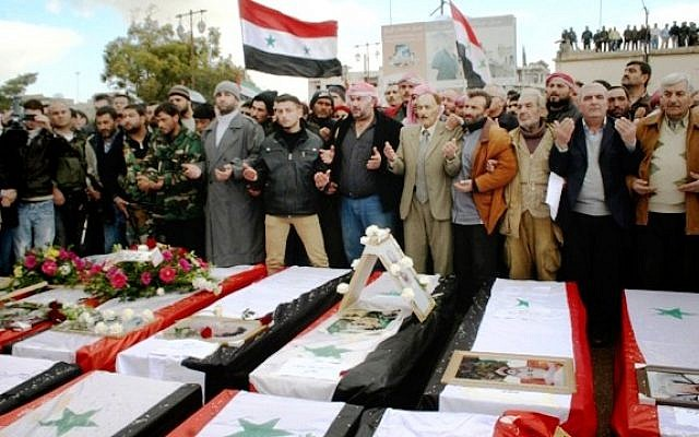 Syrians take part in a funeral procession for those killed in a car bomb explosion at the headquarters of a pro-government militia in Hama province, Syria, on Wednesday (photo credit: AP/SANA)