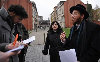 Moshe Friedman and his wife, Lea Rosenzweig, hold an improvised press conference outside Antwerp's Benoth Jerusalem, an all-female Haredi school forced by a Belgian judge to educate their sons. (Cnaan Liphshiz via JTA)