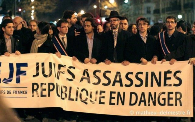 """Members of the Union of French Jewish Students demonstrate in Paris with a sign that reads, """"Jews murdered, republic in danger."""" (Courtesy UEJF)"""