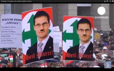 Protesters in Budapest hold signs showing Jobbik party member Marton Gyöngyosi depicted as Hitler, backed by the icon of the World War II-era Hungarian Arrow Cross party. (Screen capture from Youtube/Euronews)