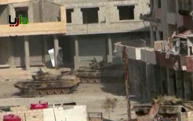 A pair of what activists say are Syrian army tanks sit in a street in the Daraya neighborhood of Damascus on January 25, 2013. (AP Photo/Sham News Network via AP video)