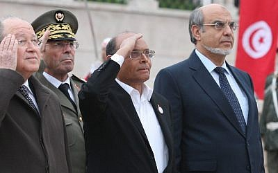 Tunisian Prime Minister Hamadi Jebali, right, President Moncef Marzouki, center, and head of constitutional assembly Mustapha Ben Jaafar, left, salute the national flag during a ceremony marking the second anniversary of the Revolution, Monday, January 14, 2013, in Tunis (photo credit: AP)