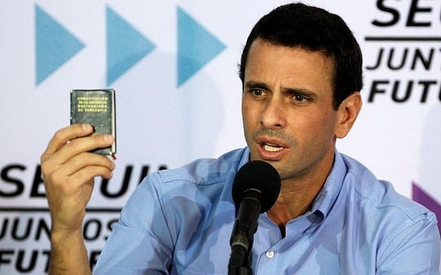 Venezuela's opposition leader Henrique Capriles Radonski holds up a miniature copy of the national constitution during a news conference in Caracas, Venezuela in January, 2013 (photo credit: AP/Fernando Llano)