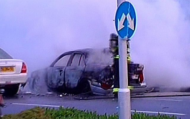 The charred husk of a car that was targeted by a bomb in Tel Aviv  (illustrative photo credit: Channel 2 screenshot)