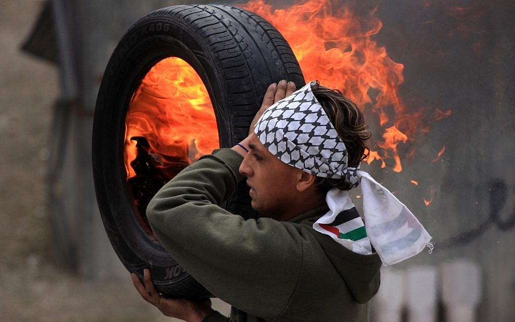 A Palestinian protester holds a burning tire during clashes with Israeli forces in the Qalandia refugee camp (photo credit: Issam Rimawi/Flash90)