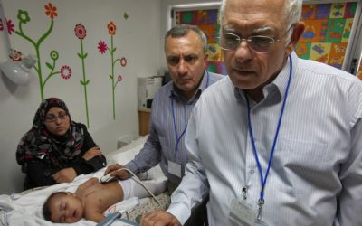 Paediatric cardiologists Dr. Akiva Tamir of Wolfson Medical Center and Dr. Omar Assali from Nablus's Rafidiya hospital examine a Palestinian child as part of Save a Child's Heart, an organization funded by the EU (photo credit: Flash90/David Silverman)