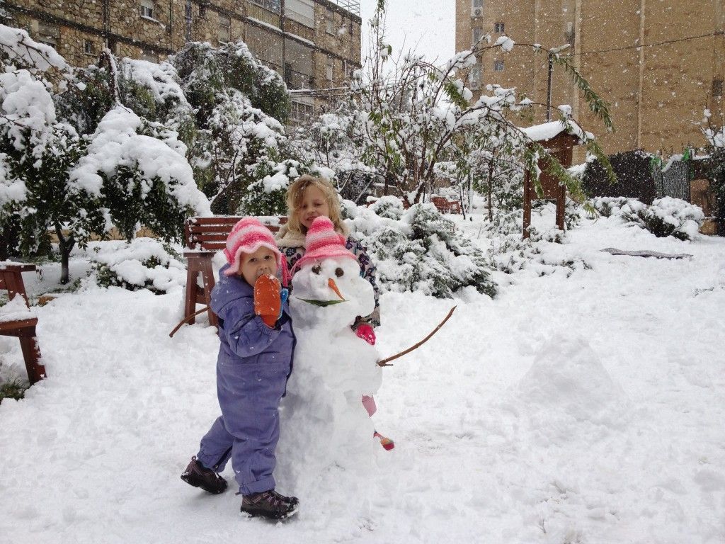 A girl hugging a snowman (photo credit: Mitch Ginsburg/Times of Israel staff)